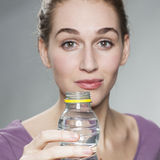 Radiant 20s girl wearing purple shirt showing a bottle of citrus mineral water in foreground Royalty Free Stock Photos
