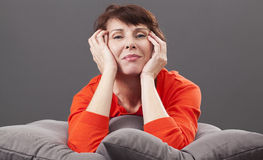 Radiant smiling 50s woman laid on cushions with happiness Royalty Free Stock Images