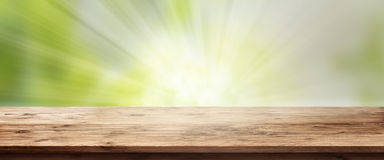 Radiant spring background with wooden table. Radiant green spring background with empty rustic wooden table for a concept Royalty Free Stock Photos