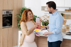 Radiant wife discussing nursery colours with husband stock photography