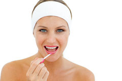 Radiant woman applying gloss Royalty Free Stock Image