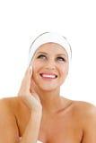 Radiant woman applying a make-up base Stock Image