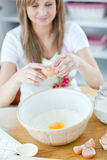 Radiant woman breaking eggs in a bowl. In the kitchen at home Stock Photo