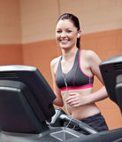 Radiant woman with earphones running on treadmill Stock Photo