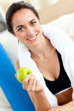Radiant woman eating an apple after working out Stock Photo