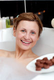 Radiant woman eating chocolate while having a bath Royalty Free Stock Photos