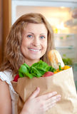 Radiant woman holding a grocery bag Stock Image