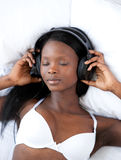 Radiant woman listening music lying on her bed Stock Photos