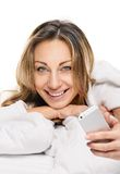 Radiant woman with phone lying on bed Stock Image