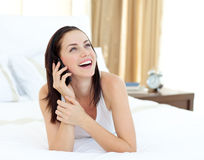Radiant woman on phone lying on her bed Royalty Free Stock Photography