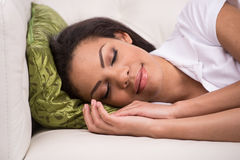 Radiant woman sleeping on sofa in living room. Royalty Free Stock Image