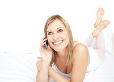 Radiant woman talking on phone lying on her bed. Portrait of a radiant woman talking on phone lying on her bed Royalty Free Stock Photos