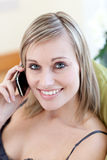 Radiant woman talking on phone sitting on a sofa Stock Photo
