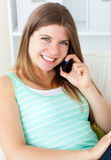 Radiant woman talking on phone sitting on a sofa Stock Images