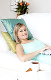 Radiant woman using a laptop lying on a sofa Royalty Free Stock Photography