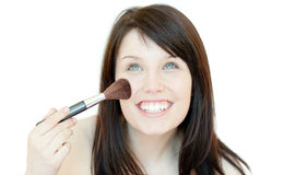 Radiant woman using a powder brush. Against a white background Stock Photos