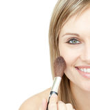 Radiant woman using a powder brush. Against a white background Stock Image