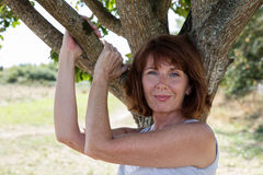 Radiant young aging woman touching a tree with sensuality. Senior green wellness - gorgeous smiling mature woman holding tree branches in harmony with nature Royalty Free Stock Photography