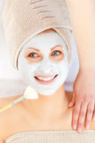 Radiant young woman having white cream on her face Stock Photos