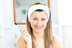 Radiant young woman using mascara in the bathroom Stock Photography