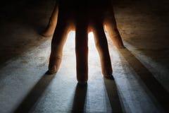 Radiates Rays of Light shine through silhouette of hand Royalty Free Stock Image