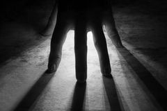 Radiates Rays of Light shine through silhouette of hand in black Stock Images