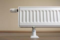 Radiateur de chauffage avec le bouton thermostatique dans le salon photo libre de droits