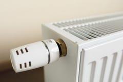 Radiateur de chauffage avec le bouton thermostatique dans le salon photographie stock libre de droits