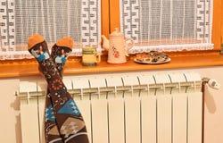 Radiateur et femme de chauffage central dans les chaussettes rayées image stock