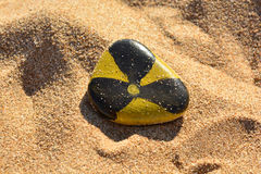 Radiation sign painted paints on a stone on the beach Royalty Free Stock Photo