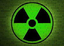 Radiation sign on a wall. Green radiation sign on a brick wall Royalty Free Stock Photo