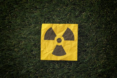 Radiation warning sign on a green grass Royalty Free Stock Image