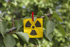 Radiation warning sign hanging on a tree Stock Photography