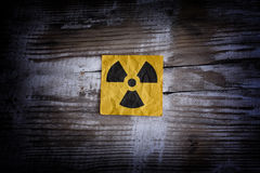 Radiation warning sign on a wooden surface Royalty Free Stock Photos