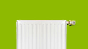 Radiator. White radiator with thermostat on green wall Royalty Free Stock Image