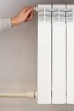 Radiator adjustment closeup. Woman`s hand adjusting radiator temperature Stock Photos