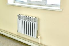 Heating white radiator under a large window. Radiator Central heating attached to wall closed windows royalty free stock image