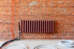Radiator en bundels van golfpijpen tegen een bakstenen muur Binnenland tijdens reparatie royalty-vrije stock foto