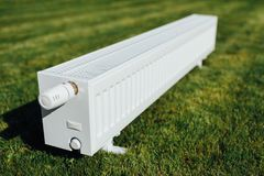 Radiator on green lawn, ecological heating concept. Closeup view Royalty Free Stock Photo