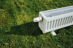 Radiator on green lawn, ecological heating concept. Closeup view Royalty Free Stock Photography