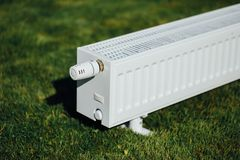 Radiator on green lawn, ecological heating concept. Closeup view Stock Photography