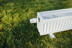 Radiator on green lawn, ecological heating concept. Closeup view Stock Image
