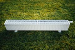Radiator on green lawn, ecological heating concept. Closeup view Royalty Free Stock Image