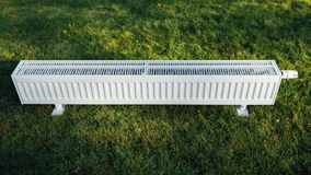 Radiator on green lawn, ecological heating concept. Closeup view Stock Photo