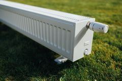 Radiator on green lawn, ecological heating concept. Closeup view Royalty Free Stock Images