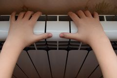 The radiator of heating warms the childs hands Royalty Free Stock Photo