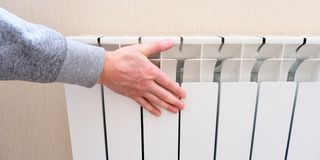 Radiator heating, white radiator in the apartment. Hand felt the coldness. Heating is turned off for non-payment. Radiator heating, white radiator in the stock photo