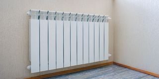 Radiator heating, white radiator in the apartment. Hand felt the coldness. Heating is turned off for non-payment. stock images