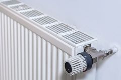 Radiator op een muur met thermostaat stock fotografie
