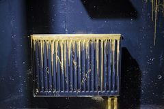 A radiator painted black with gold streaks of paint stock images